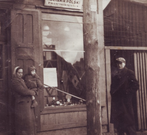 """Ul. Kościelna 23 (18.IV.1941), żona Franciszka Szmausa - Michalina z córką Barbarą przed warsztatem naprawy rowerów """"MECHANIK POLSKI"""""""